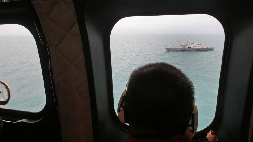 A military ship is seen from Indonesian Air Force NAS 332 Super Puma helicopter during a search operation for the victims of AirAsia Flight 8501, off Pangkalan Bun, Central Borneo, Indonesia, Tuesday, Jan. 6, 2015. The Singapore-bound plane crashed into the sea 42 minutes after taking off on Dec. 28.  (AP Photo/Achmad Ibrahim, Pool)