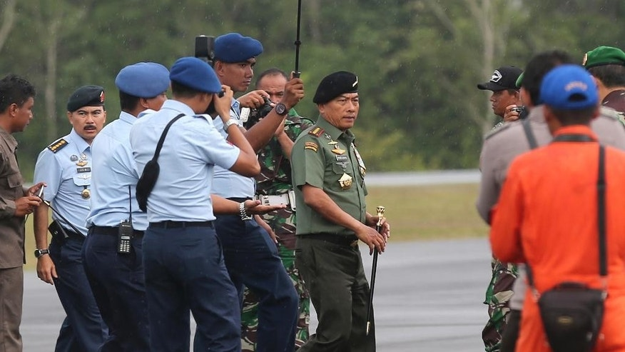 CORRECTS PHOTOGRAPHER'S NAME - Indonesian Armed Forces Chief, Gen. Moeldoko, center, walks upon arrival following a search operation for the victims of AirAsia Flight 8501 at the airport in Pangkalan Bun, Indonesia, Tuesday, Jan. 6, 2015. The search operation for AirAsia Flight 8501 will spread slightly eastward on Tuesday as the weather and currents drag wreckage in that direction, the head of Indonesia's rescue agency said. (AP Photo/Achmad Ibrahim)