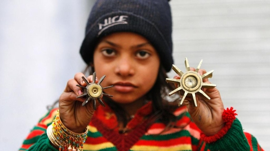 An Indian border girl displays a mortar shell allegedly fired from the Pakistan side of the border at Bainglad village in Samba sector, about 52 kilometers (32 miles) from Jammu, India, Tuesday, Jan. 6, 2015. Pakistani troops fired gunshots and mortar shells that killed an Indian soldier in northern Kashmir on Monday after a lull in the countries' cross-border firing, an Indian paramilitary official said. Pakistan blamed India for the violence and said two civilians were killed by Indian shelling. (AP Photo/Channi Anand)