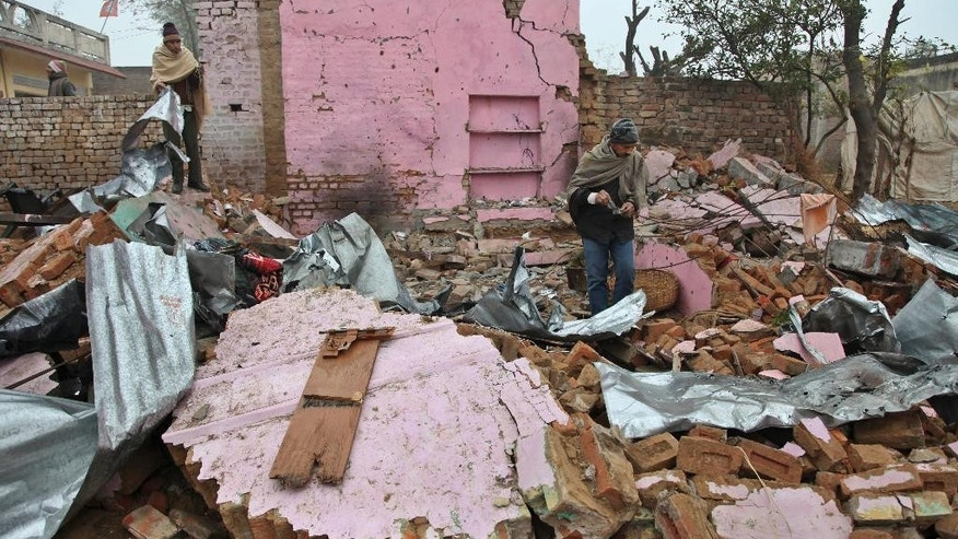 Indian villagers look for their belongings from one of the houses damaged in an alleged firing by Pakistani troops at Bainglad village in Samba sector, about 52 kilometers (32 miles) from Jammu, India, Tuesday, Jan. 6, 2015. Pakistani troops fired gunshots and mortar shells that killed an Indian soldier in northern Kashmir on Monday after a lull in the countries' cross-border firing, an Indian paramilitary official said. Pakistan blamed India for the violence and said two civilians were killed by Indian shelling. (AP Photo/Channi Anand)