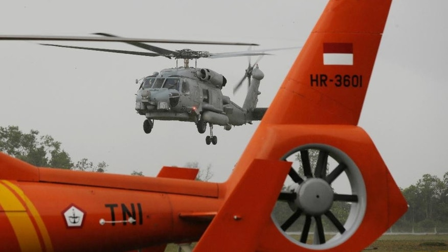 A U.S. Navy helicopter approaches to land following their search operation for the victims of AirAsia Flight 8501at the airport in Pangkalan Bun, Indonesia, Tuesday, Jan. 6, 2015. The search operation for AirAsia Flight 8501 will spread slightly eastward on Tuesday as the weather and currents drag wreckage in that direction, the head of Indonesia's rescue agency said. (AP Photo/Achmad Ibrahim)