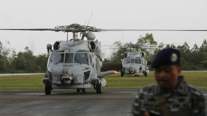 U.S. Navy helicopter taxi back upon arrival following their search operation for the victims of AirAsia Flight 8501 at the airport in Pangkalan Bun, Indonesia, Tuesday, Jan. 6, 2015. The search operation for AirAsia Flight 8501 will spread slightly eastward on Tuesday as the weather and currents drag wreckage in that direction, the head of Indonesia's rescue agency said. (AP Photo/Achmad Ibrahim)