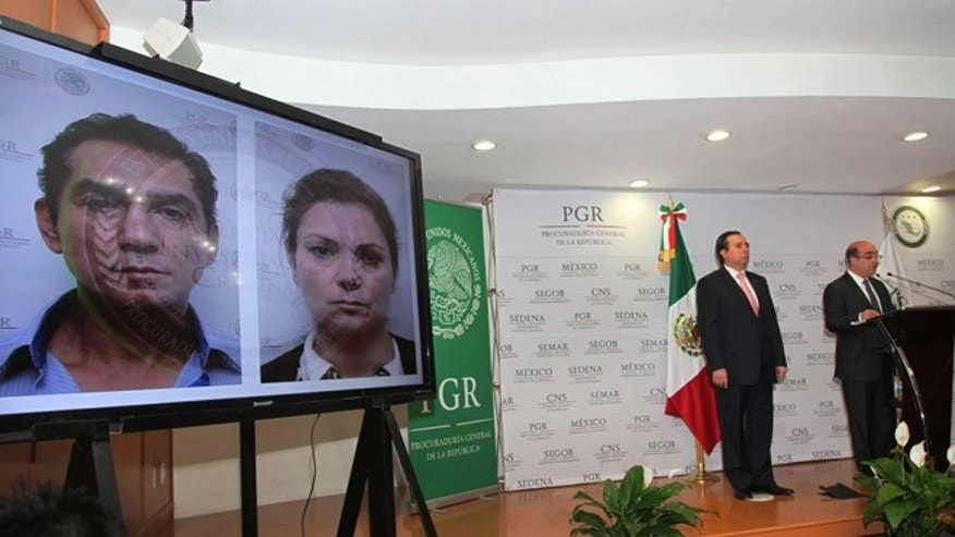 CORRECTS DAY OF THE WEEK - Mexico's Attorney General, Jesus Murillo Karam, right, flanked by Tomas Zeron director of Mexico's Criminal Investigation Agency, speaks during a news conference in Mexico City, Sunday Dec. 7, 2014. While showing a photo of the mayor of Iguala, Jose Luis Abarca and his wife, Maria de los Angeles Pineda Villa, Attorney General Murillo Karam confirmed Sunday that one of the college students missing since September, has been identified among charred remains found several weeks ago near a garbage dump. He said the student is Alexander Mora, based on material extracted from the bone fragment and analyzed by forensics experts at a laboratory in Innsbruck, Austria. The mayor and his wife are among the 80 people arrested so far for the disappearance of the students. (AP Photo/Marco Ugarte)