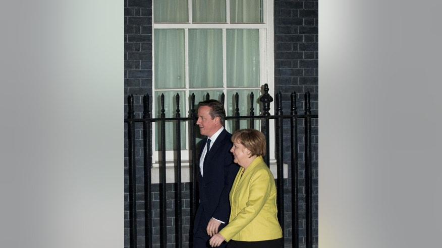British Prime Minister David Cameron and German Chancellor Angela Merkel walk together before their meeting in 10 Downing Street, London, Wednesday, Jan. 7, 2015.  The German Chancellor is in London for one of talks. (AP Photo/Matt Dunham)