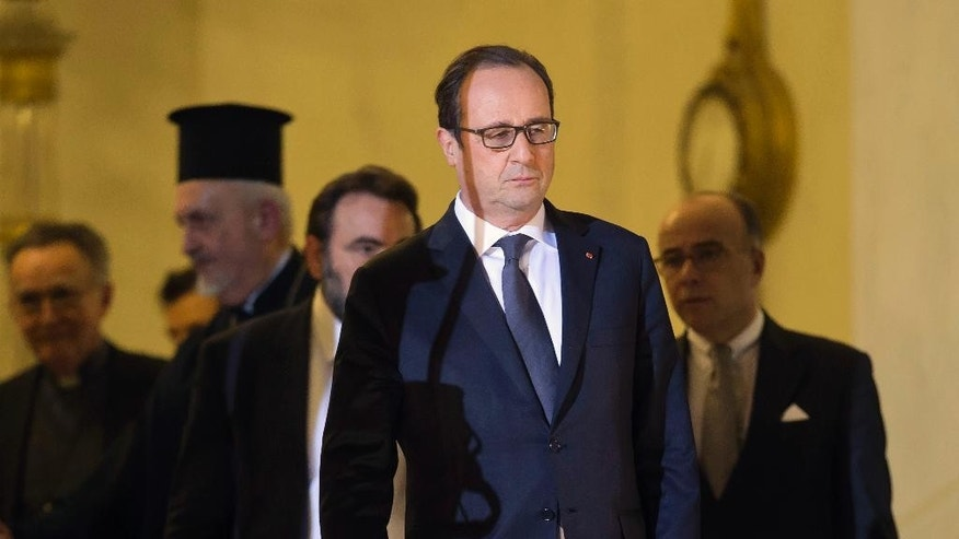 French President Francois Hollande walks out of the lobby of the Elysee Palace, after a meeting with religious leaders in Paris, Wednesday, Jan. 7, 2015. Masked gunmen stormed the offices of a French satirical newspaper Wednesday, killing at least 12 people before escaping, police and a witness said. The weekly has previously drawn condemnation from Muslims. (AP Photo/Michel Euler)