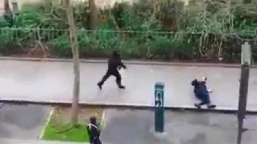 Masked gunman run towards a victim of their gun fire  outside the  French satirical newspaper Charlie Hebdo's office, in Paris, Wednesday, Jan. 7, 2015. Paris residents captured chilling video images of two masked gunmen shooting a police officer after an attack at a French satirical newspaper. In the video, the gunmen armed with assault rifles are seen running up to an injured police officer, who lies squirming on the ground. The police officer raises his hands up before one of the assailants shoots him in the head at a close range.  (AP Photo) NO SALES
