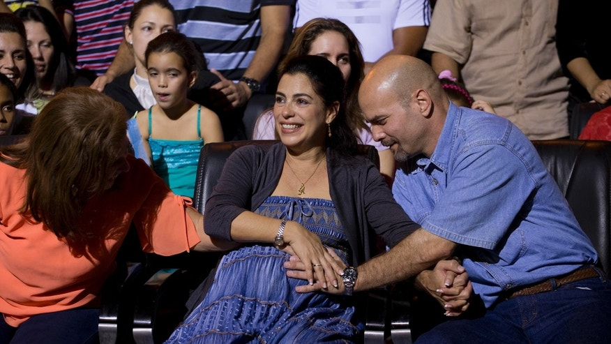 """Gerardo Hernandez, right, member of """"The Cuban Five,"""" touches the belly of his pregnant wife Adriana Perez during a concert in Havana, Cuba. The wife of the Cuban intelligence agent freed by the United States in December gave birth to a girl Tuesday, Jan. 6, 2015, after a pregnancy made possible by negotiations to improve ties between the two countries. U.S. officials helped facilitate a process of artificial insemination for Hernandez and his wife. (AP Photo/Ramon Espinosa, File)"""