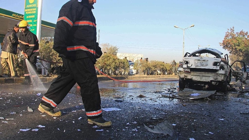 Afghan firefighters clear the site of a blast that killed a provincial judge in Jalalabad, capital of Nangarhar province, Afghanistan Wednesday, Jan. 7, 2015. Authorities said insurgent attacks across Afghanistan have killed several people, including Nangarhar provincial judge Mohammad-ul Hassan. (AP Photo)