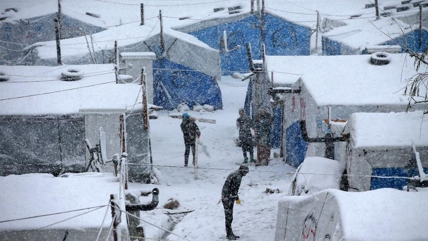 Syrians stand between their tents as they prepare to remove the snow from the top of their tents at a refugee camp in Deir Zannoun village, in the Bekaa valley, east Lebanon, Wednesday, Jan. 7, 2015. While the storm disrupted life for everyone, it proved particularly trying for the hundreds of thousands of Syrian refugees who live in tents and makeshift shelters in the Bekaa. The storm dumped rain and hail on Lebanon's coast and heavy snows in the mountains and central Bekaa Valley, where gas stations, banks, schools and most shops closed. (AP Photo/Hussein Malla)