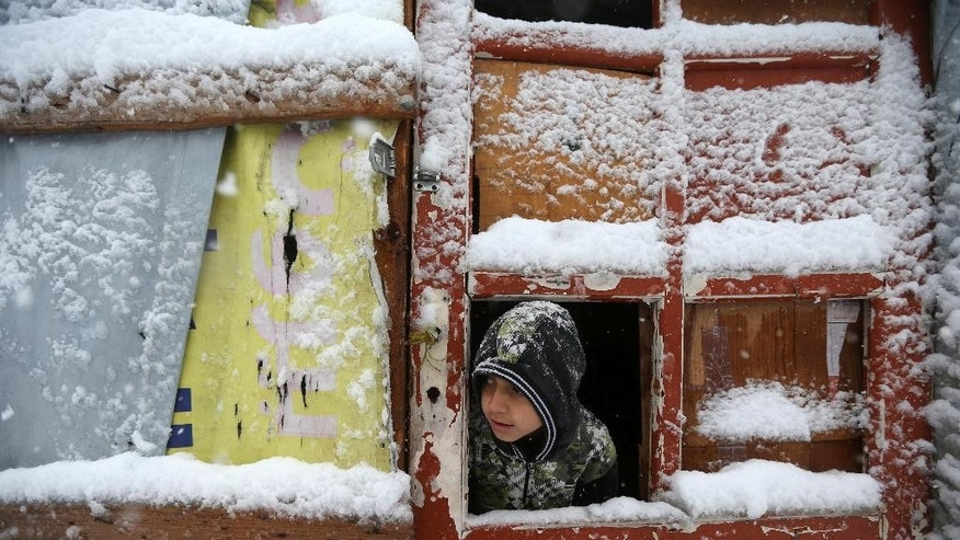 A Syrian boy looks out through his tent door covered in snow at a refugee camp in Deir Zannoun village, in the Bekaa valley, east Lebanon, Wednesday, Jan. 7, 2015. While the storm disrupted life for everyone, it proved particularly trying for the hundreds of thousands of Syrian refugees who live in tents and makeshift shelters in the Bekaa. The storm dumped rain and hail on Lebanon's coast and heavy snows in the mountains and central Bekaa Valley, where gas stations, banks, schools and most shops closed. (AP Photo/Hussein Malla)