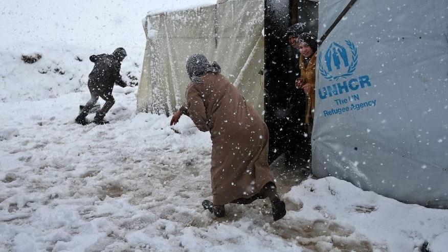 Syrians throw snow at each other at a refugee camp in Deir Zannoun village, in the Bekaa valley, east Lebanon, Wednesday, Jan. 7, 2015. While the storm disrupted life for everyone, it proved particularly trying for the hundreds of thousands of Syrian refugees who live in tents and makeshift shelters in the Bekaa. The storm dumped rain and hail on Lebanon's coast and heavy snows in the mountains and central Bekaa Valley, where gas stations, banks, schools and most shops closed. (AP Photo/Hussein Malla)