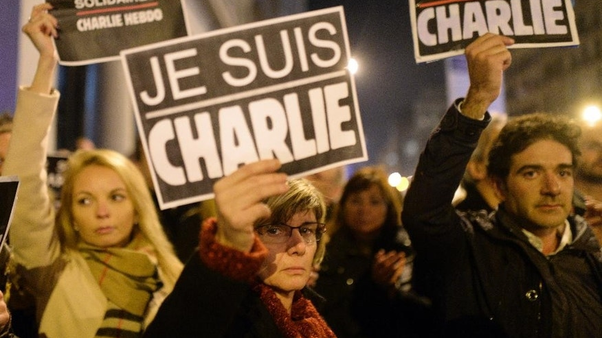 People attend a demonstration in solidarity with those killed in an attack at the Paris offices of weekly newspaper Charlie Hebdo, at the French Consulate in Barcelona, Spain, Wednesday, Jan 7, 2015. Masked gunmen stormed the Paris offices of a weekly newspaper that caricatured the Prophet Muhammad, methodically killing 12 people Wednesday, including the editor, before escaping in a car. It was France's deadliest postwar terrorist attack. (AP Photo/Manu Fernandez)
