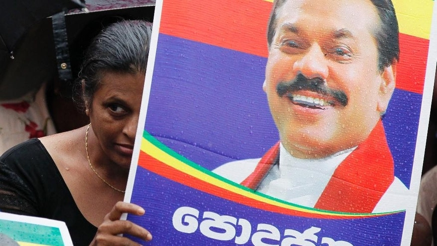 In this Wednesday, Dec. 24, 2014 photo, a supporter holds a poster of Sri Lankan President Mahinda Rajapaksa and attends an election campaign rally in the rain in Colombo, Sri Lanka. Rajapaksa faces a fierce political battle after a onetime close ally, former Health Minister Maithripala Sirisena, suddenly defected from the ruling party to run against him in Thursday's presidential election. While Rajapaksa's campaign centers around his military victory and his work rebuilding the country's infrastructure and economy, Sirisena's focuses on reining in the president's expanding powers. He also accuses Rajapaksa of corruption, a charge the president denies. (AP Photo/Eranga Jayawardena)