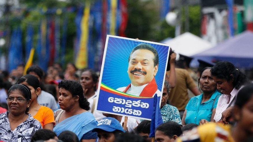 In this Wednesday, Dec. 24, 2014 photo, supporters hold a poster of Sri Lankan President Mahinda Rajapaksa during his election campaign rally in Colombo, Sri Lanka. Rajapaksa faces a fierce political battle after a onetime close ally, former Health Minister Maithripala Sirisena, suddenly defected from the ruling party to run against him in Thursday's presidential election. While Rajapaksa's campaign centers around his military victory and his work rebuilding the country's infrastructure and economy, Sirisena's focuses on reining in the president's expanding powers. He also accuses Rajapaksa of corruption, a charge the president denies. (AP Photo/Eranga Jayawardena)