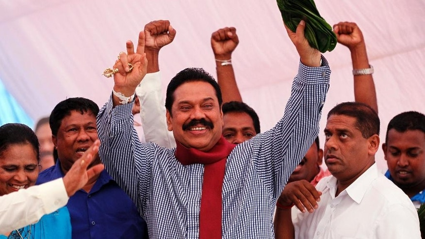 In this Wednesday, Dec. 24, 2014 photo, Sri Lankan President Mahinda Rajapaksa greets supporters during his election campaign rally in Colombo, Sri Lanka. Rajapaksa faces a fierce political battle after a onetime close ally, former Health Minister Maithripala Sirisena, suddenly defected from the ruling party to run against him in Thursday's presidential election. While Rajapaksa's campaign centers around his military victory and his work rebuilding the country's infrastructure and economy, Sirisena's focuses on reining in the president's expanding powers. He also accuses Rajapaksa of corruption, a charge the president denies. (AP Photo/Eranga Jayawardena)