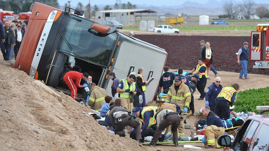 Emergency personnel tend to victims of a tour bus crash on an agricultural sightseeing trip Jan. 8, 2015, in Yuma, Ariz.