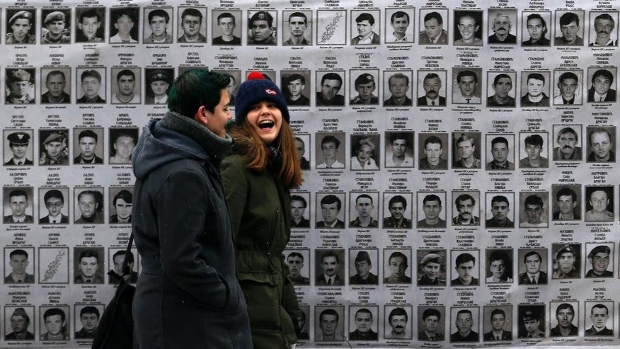 "A couple walks past a banner with pictures of Serbs, presumed killed by NATO and ethnic Albanian separatists in Kosovo, in front of the Serbia's war crimes court in Belgrade, Serbia, Thursday, Jan. 8, 2015. Serbia's war crimes prosecutor Vladimir Vukcevic says his office has faced an orchestrated ""campaign of lynch"" by war criminals and nationalists _ including accusations of spying from the U.S. leveled by ruling party officials _ after it recently moved to open sensitive cases from the Balkan country's wartime past. (AP Photo/Darko Vojinovic)"