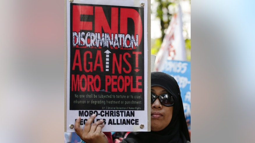 FILE - In this Dec. 3, 2014 file photo, Filipino Muslim Munarassana Muctar-Jandul displays a placard as she joins a rally by activists in front of the Justice Department in Manila, Philippines, to protest the continuing detention of her husband Ainbasa Balitung Jandul whom she claimed was mistaken for an Abu Sayyaf member named Abdasil Dima. In the country's dogged pursuit of terror suspects, Philippine law enforcers have made a slew of mistaken arrests in going after Abu Sayyaf and other Islamic militant groups long active in this Southeast Asian nation's south. (AP Photo/Bullit Marquez, File)