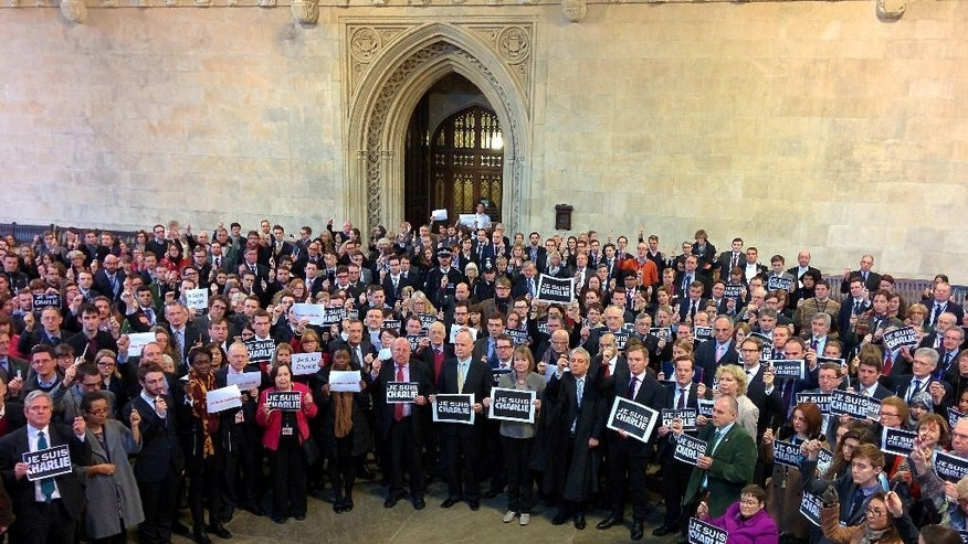 Members of Parliament stand in Westminster Hall, London, holding pens in solidarity with those affected by the Charlie Hebdo massacre in France, Thursday, Jan. 8, 2015. French police hunted Thursday for two heavily armed men — one with a terrorism conviction and a history in jihadi networks — in the methodical killing of 12 people at a satirical newspaper that caricatured the Prophet Muhammad. (AP Photo/PA,Tim Sculthorpe)
