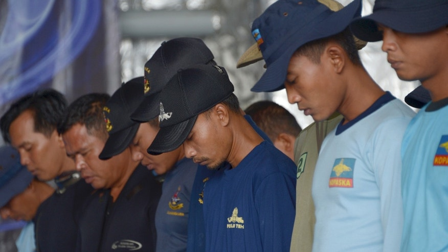 Jan. 8, 2015: Indonesian navy divers pray on the navy vessel KRI Banda Aceh prior to dive in an area where a team found the tail of AirAsia Flight 8501 on the Java Sea.