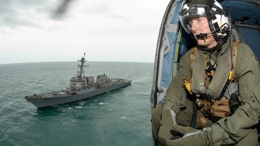 Jan. 6, 2015: Naval aircrewman 2nd Class Cody Witherspoon helps in the search for missing AirAsia Flight 8501 in the Java Sea, as his helicopter returns to the USS Sampson. (AP Photo/U.S. Navy, Petty Officer 1st Class Brett Cote)