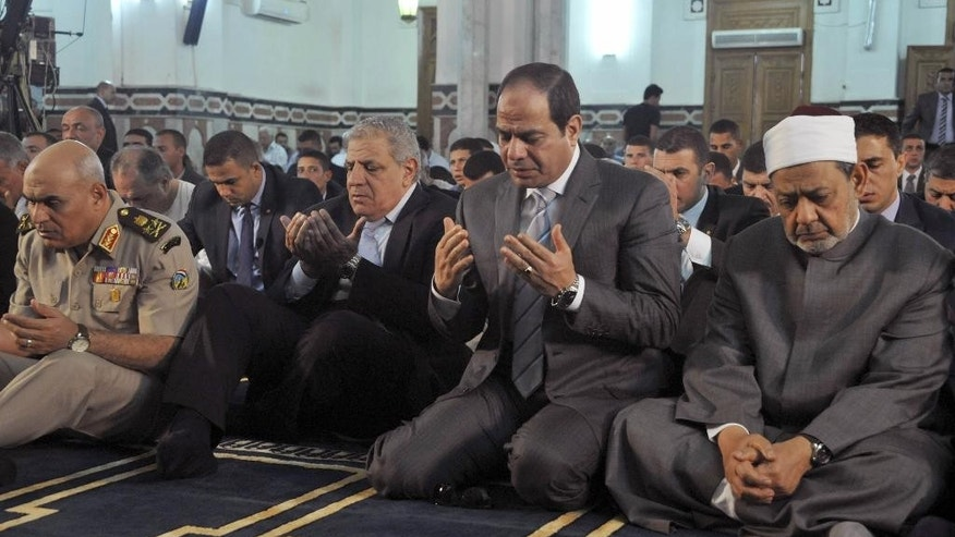 "FILE - In this Oct. 4, 2014 file photo released by Egypt's official Middle East News Agency (MENA) shows Egyptian President  Abdel-Fattah el-Sissi, second right, the Grand Sheik of Al-Azhar, Ahmed el-Tayeb, right, Prime Minister Ibrahim Mehleb, center, and others praying on the first day of Eid al-Aha, or Feast of Sacrifice, in Cairo, Egypt. El-Sissi opened 2015 with a dramatic call for a ""revolution"" in Islam. His professed goal is to purge the religion of extremist ideas of intolerance and violence that fuel groups like al-Qaida and the Islamic State - and lie behind Tuesday's attack in Paris on a French satirical newspaper that killed 12 people. (AP Photo/MENA, File)"