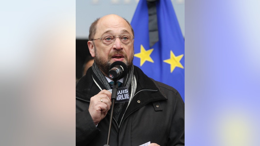 European Parliament President Martin Schulz shows a sticker that reads: 'Je suis Charlie (I Am Charlie)', during a gathering to pay respect to the victims of Wednesday's terror attack in Paris, in front of the European Parliament in Brussels, Thursday, Jan. 8, 2015. Eight journalists, two police officers, a maintenance worker and a visitor were killed, and eleven people wounded in a terrorist attack against French satirical newspaper Charlie Hebdo in Paris. (AP Photo/Yves Logghe)
