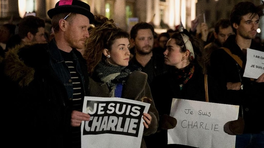 "People hold up posters reading 'I am Charlie' in French as they take part in a vigil of people, including many who were French, to show solidarity with those killed in an attack at the Paris offices of weekly newspaper Charlie Hebdo, in Trafalgar Square, London, Wednesday, Jan. 7, 2015. Masked gunmen shouting ""Allahu akbar!"" stormed the Paris offices of the satirical newspaper Charlie Hebdo, killing at least 12 people, including the paper's editor and a cartoonist, before escaping in a getaway car.  (AP Photo/Matt Dunham)"