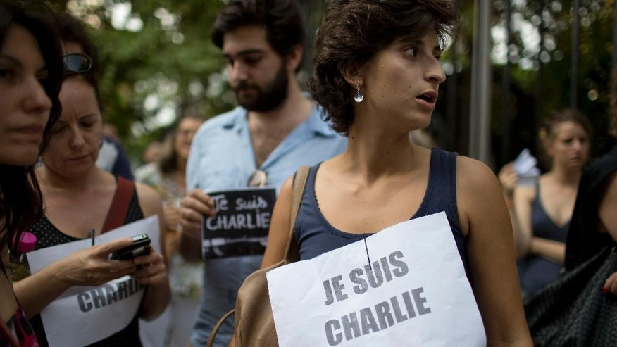 "People stand outside France's embassy wearing signs that read in French ""I am Charlie"" in solidarity with those killed in an attack at the Paris offices of the weekly newspaper Charlie Hebdo in Buenos Aires, Argentina, Wednesday, Jan. 7, 2015. Masked gunmen stormed the the satirical newspaper that caricatured the Prophet Muhammad, methodically killing 12 people Wednesday, including the editor, before escaping in a car. It was France's deadliest postwar terrorist attack. (AP Photo/Natacha Pisarenko)"