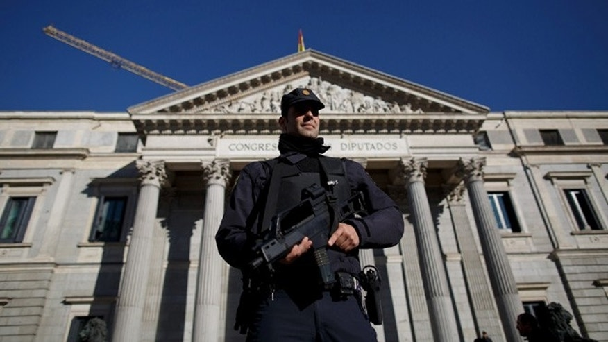 MADRID, SPAIN - JANUARY 08:  An armed policeman stands guard after members of the Spanish Parliament and the French Ambassador to Spain Jerome Bonnafont paid a minute of silence at midday in front of the Spanish Parliament in solidarity with victims of yesterday's terrorist attack in Paris on January 8, 2015 in Madrid, Spain. France is on maximum security threat level after twelve people were killed yesterday, including two police officers, at the offices of the satirical magazine Charlie Hebdo in Paris. (Photo by Pablo Blazquez Dominguez/Getty Images)