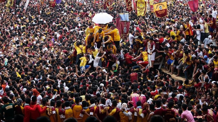 Filipino devotees prepare to move the carriage bearing the image of the Black Nazarene, center, for its annual procession to celebrate its feast day Friday, Jan. 9, 2015 in Manila, Philippines. The raucous celebration drew tens of thousands of devotees in a barefoot procession around Manila streets. (AP Photo/Bullit Marquez)