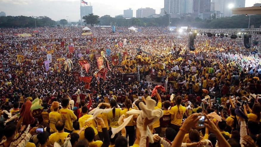 Filipino devotees wave handkerchiefs to cheer the image of the Black Nazarene, center, during its annual procession to celebrate its feast day Friday, Jan. 9, 2015 in Manila, Philippines. The raucous celebration drew tens of thousands of devotees in a barefoot procession around Manila streets. (AP Photo/Bullit Marquez)