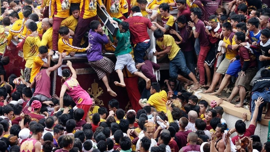 Filipino devotees cling to kiss the cross of the Black Nazarene during a procession to celebrate its feast day Friday, Jan. 9, 2015 in Manila, Philippines. The raucous celebration drew tens of thousands of devotees in a barefoot procession around Manila streets. (AP Photo/Bullit Marquez)