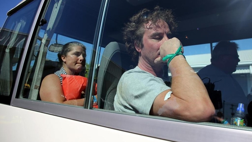 Tourists who were rescued after a catamaran sank off the Pacific coast of Costa Rica wait inside a bus, in the port of Caldera, Costa Rica, Thursday, Jan. 8, 2015. The catamaran carrying foreign tourists was on a pleasure cruise when it capsized, emergency officials said. The boat that was on a day trip to the popular Tortuga Island, sank about 9 miles off the country's Pacific Coast. (AP Photo/Enrique Martinez)