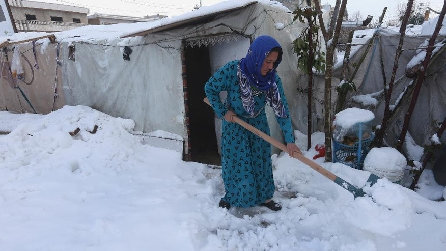 A Syrian woman removes snow from around her tent at a refugee camp in al-Majdal village, Bekaa valley, east Lebanon, Thursday, Jan. 8, 2015. Snow fell in the Middle East as a powerful winter storm swept through the region, killing at least two Syrian refugees in Lebanon and forcing thousands of others who have fled their country civil war to huddle for warmth in refugee camps. (AP Photo/Hussein Malla)