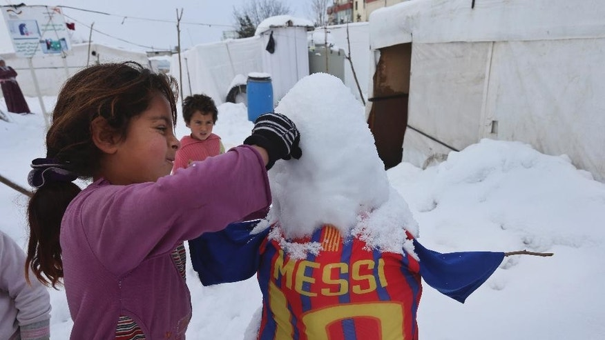 A Syrian girl makes a snowman outside her tent at a refugee camp in al-Majdal village, Bekaa valley, east Lebanon, Thursday, Jan. 8, 2015. Snow fell in the Middle East as a powerful winter storm swept through the region, killing at least two Syrian refugees in Lebanon and forcing thousands of others who have fled their country civil war to huddle for warmth in refugee camps. (AP Photo/Hussein Malla)