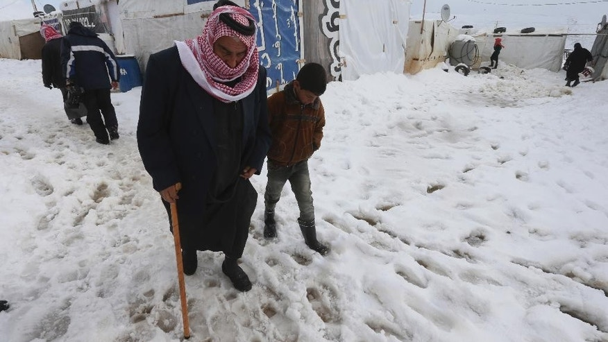 An old Syrian man helped by his grandson walks on the snow at their refugee camp in al-Faour village, Bekaa valley, east Lebanon, Thursday, Jan. 8, 2015. Snow fell in the Middle East as a powerful winter storm swept through the region, killing at least two Syrian refugees in Lebanon and forcing thousands of others who have fled their country civil war to huddle for warmth in refugee camps. (AP Photo/Hussein Malla)