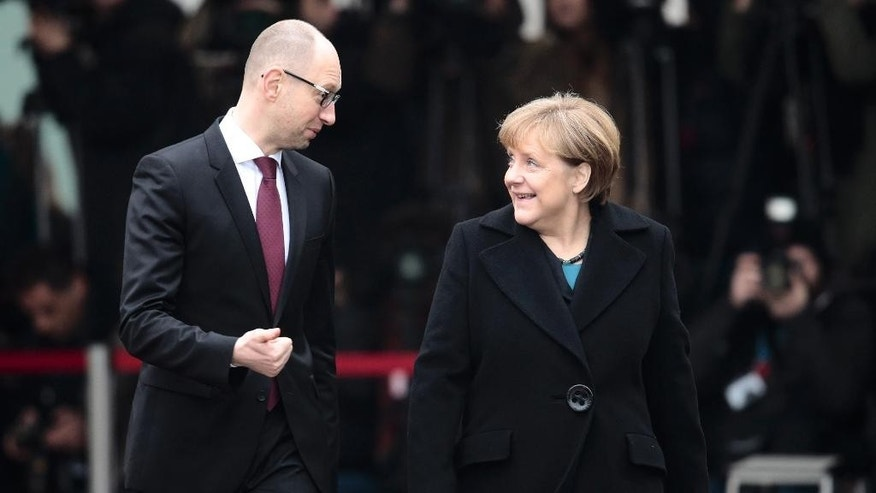 German Chancellor Angela Merkel, right, welcomes the Prime Minister of Ukraine Arseniy Yatsenyuk at the chancellery in Berlin, Thursday, Jan. 8, 2015. Merkel and Yatsenyuk meet for bilateral talks in Berlin. (AP Photo/Markus Schreiber)