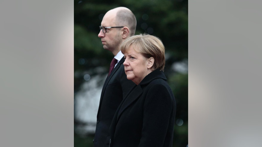 German Chancellor Angela Merkel, right, and the Prime Minister of Ukraine Arseniy Yatsenyuk, left, listen to the national anthems during the welcoming ceremony at the chancellery in Berlin, Thursday, Jan. 8, 2015. Merkel and Yatsenyuk meet for bilateral talks in Berlin. (AP Photo/Markus Schreiber)