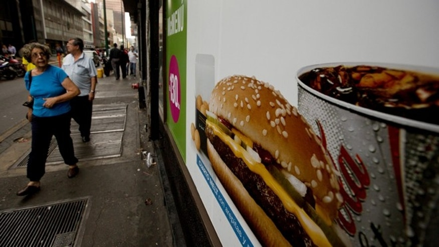 A customer glances at a McDonalds' banner menu showing a burger accompanied by arepas or corn cakes, instead of fries, in Caracas, Venezuela, Tuesday, Jan. 6, 2015. McDonalds franchises in Venezuela have run out of potatoes and are now serving South American alternatives like deep-fried arepas or yuca, a starchy tuberous root. The franchisers are blaming a contract dispute with West Coast dock workers for halting the export of frozen fries to the country. (AP Photo/Fernando Llano)
