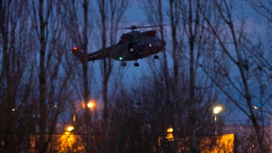 A helicopter flies over a building, where the suspects of a shooting at a Paris newspaper office were holed up, after security forces stormed it in Dammartin-en-Goele, France, Friday Jan. 9, 2015. French police stormed a printing plant north of Paris on Friday, freeing a hostage and killing two brothers linked to al-Qaida who were suspected of slaying 12 people at a Paris newspaper two days ago. (AP Photo/Peter Dejong)