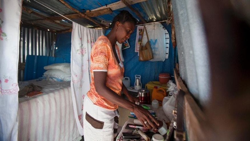 "Rosena Dordor, 40, arranges her one-room shack in a settlement in the arid hills north of the Capital in Port-au-Prince, Haiti, Friday, Jan. 9, 2014. ""We love this place because we have made it our home with our own hands and hearts,"" the 40-year-old said on a recent morning. The area was initially only meant to house those stuck in tent shelters considered most at risk for floods or landslides, but it is growing so fast that U.S. State Department officials say the settlement could soon be considered Haiti's second largest city. ( AP Photo/Dieu Nalio Chery)"