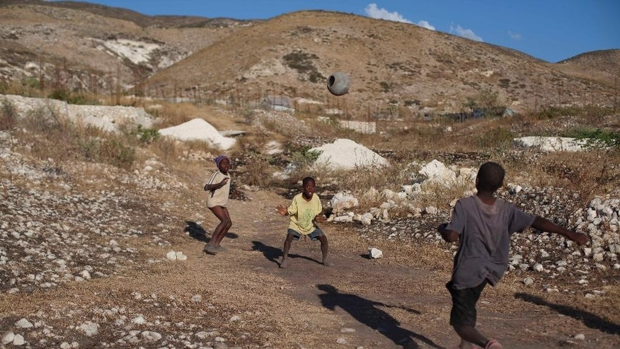 Children play soccer at a settlement on the arid hills north of the Capital in Port-au-Prince, Haiti, Friday, Jan. 9, 2014. The area was initially only meant to house earthquake refugees stuck in tent shelters considered most at risk for floods or landslides, but it is growing so fast that U.S. State Department officials say the settlement could soon be considered Haiti's second largest city. ( AP Photo/Dieu Nalio Chery)