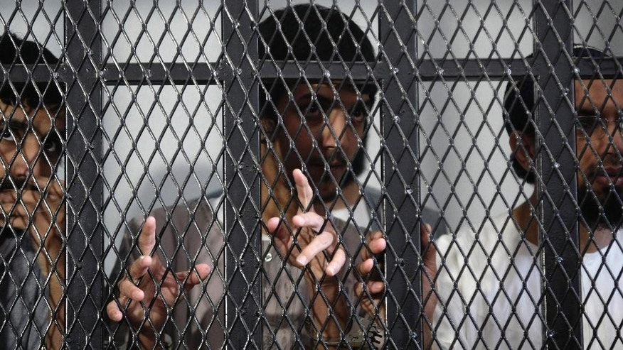 FILE - In this Thursday, Sept. 12, 2013 file photo, Saudi alleged al-Qaida militants stand behind bars during a hearing in state security court in Sanaa, Yemen. Al-Qaida in the Arabian Peninsula, suspected of having ties to the attackers in Paris, has been the most active of the terror network's branches in trying to strike in the West. (AP Photo/Hani Mohammed, File)
