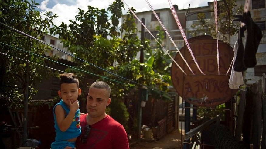 A day after his release, dissident Miguel Alberto Ulloa, 25, holds his son, as he walks beside a water tank painted with the acronym for the United States and his country's name, outside his home, in Havana, Cuba, Friday, Jan. 9, 2015. Advocates, relatives and dissidents say that Cuba has freed at least 38 people on a U.S. list of imprisoned opposition members. U.S. officials said Friday after weeks of virtual silence that those released had been on the list of 53. (AP Photo/Ramon Espinosa)
