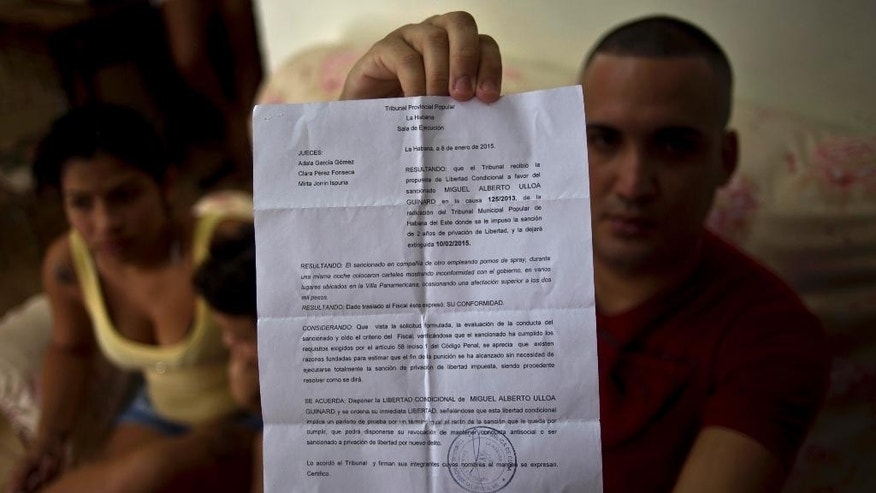 Dissident Miguel Alberto Ulloa, 25, poses for a photo in his home, holding his release document, a day after his release, in Havana, Cuba, Friday, Jan. 9, 2015. Advocates, relatives and dissidents say that Cuba has freed at least 38 people on a U.S. list of imprisoned opposition members. U.S. officials said Friday after weeks of virtual silence that those released had been on the list of 53. (AP Photo/Ramon Espinosa)