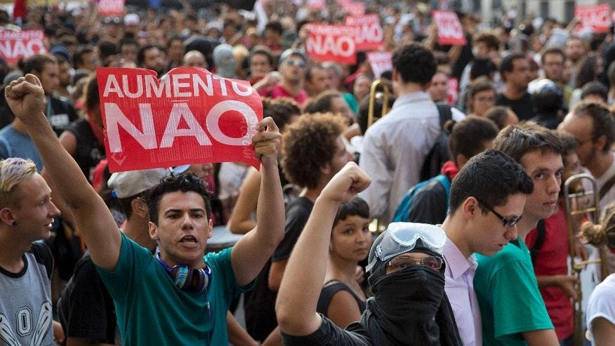 "Demonstrators holding signs that read in Portuguese ""No Rise,"" protest against a rise of public transportation fares in Sao Paulo, Brazil, Friday, Jan. 9, 2015. A few thousand people took to the streets of Brazil's biggest city to protest over an 18-cent increase in bus and subway fares. (AP Photo/Andre Penner)"