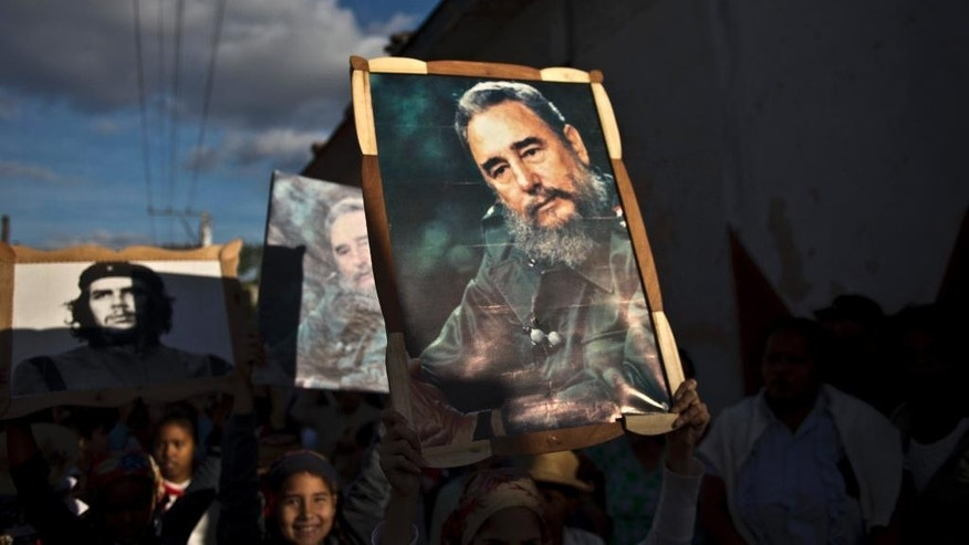 Children carry framed images of Fidel Castro and Che Guevara in a caravan tribute marking the 56th anniversary of the original street party that greeted a triumphant Castro and his rebel army, in Regla, Cuba, Thursday, Jan. 8, 2015. Castro and his rebels arrived in Havana via caravan on the first week of January 1959, after toppling dictator Fulgencio Batista. The revolutionary leader and former president has not spoken publicly on the historic Dec. 17th US-Cuba detente. (AP Photo/Ramon Espinosa)