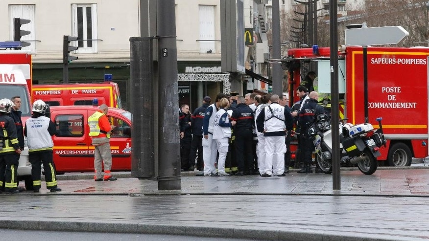 Emergency services workers arrive at a hostage-taking situation at a kosher market in Paris, Friday Jan. 9, 2015. France's anti-terrorism prosecutor says a shooting and hostage-taking attack is underway at a kosher market on the eastern edge of Paris. A police official said there are multiple hostages and wounded at the scene. (AP Photo/Francois Mori)