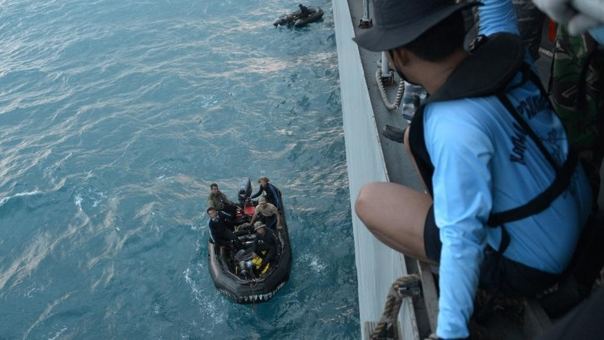 Indonesian navy divers prepare operations to lift the tail of AirAsia Flight 8501 in Java sea, Indonesia Friday, Jan. 9, 2015. Days after sonar detected apparent wreckage, an unmanned underwater vehicle showed the plane's tail, lying upside down and partially buried in the ocean floor. (AP Photo/Adek Berry, Pool)